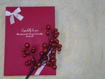 Closed box red gift with a branch of red berries on beige paper. Closed box large red gift with a branch of red berries on top lies on beige crumpled paper Royalty Free Stock Images