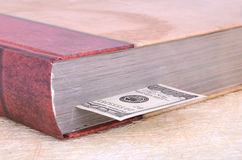 Closed brown book with a bookmark 100 USD. Closed brown book with a bookmark 100 dollars on the light background Stock Images