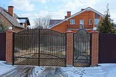 Closed brown gates and part of the fence in the street near the road in the snow. Closed private brown gates and part of the fence in the street near the road in royalty free stock photos