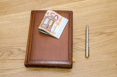 Closed brown luxury notepad with ball pen and some euro banknotes Royalty Free Stock Photo