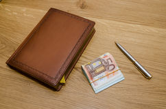 Closed brown luxury notepad with ball pen and some euro banknotes Royalty Free Stock Images