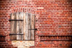Closed brown red wooden window with rusted metal hinges on a grungy red brick wall. Of an old barn weathered by exposure to the elements Royalty Free Stock Photo