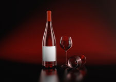 Closed Burgundy red wine bottle. Closed Burgundy red wine bottle with empty label and two glasses on red black background with reflections. Highly detail render Royalty Free Stock Photo