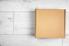 Closed cardboard box. On wooden floor royalty free stock photo