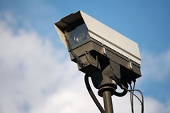 Closed-circuit television (CCTV). CCTV camera against a blue sky with clouds Royalty Free Stock Image