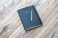 Closed planner with pen is on a wooden desk. Royalty Free Stock Images