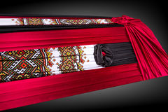 Closed coffin covered with authentic ukrainian cloth  on gray background. Royalty Free Stock Images