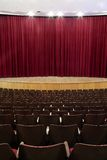 Closed curtain. Cinema, theater interior; closed red velvet curtain, wooden seats Royalty Free Stock Photography