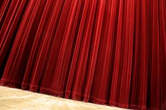 Closed curtain. Red velvet closed curtain, tilted photo, wooden floor Stock Images