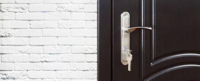 Closed dark brown wooden door handle with lock. Royalty Free Stock Photo