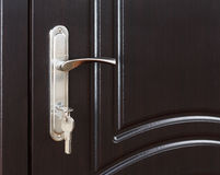 Closed dark brown wooden door handle with lock. Stock Photography