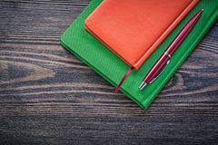 Closed diary books ball-point pen on vintage wooden board educat Royalty Free Stock Photos