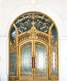 Closed door of building with gold ornate pattern. Beautiful arched doorway. Door made of wood, gold and glass reflecting arch. White wall of building with Stock Image