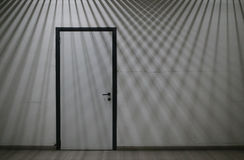 Closed door with crossing lines of lights and shadows falling on Royalty Free Stock Image