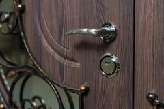 Closed door handle. Door lock. Dark brown wooden door closeup. Modern interior design, door handle. New house concept. Real estate. Closed door.Dark brown wooden Stock Images