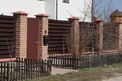Closed door and a fence of brown wooden planks and bricks on the street with bushes. A closed door and a long fence of brown wooden planks and bricks on the royalty free stock photos