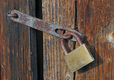 Closed door with padlock. Closed woody door with old rust padlock Royalty Free Stock Photo