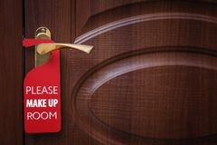 Closed door with sign PLEASE MAKE UP ROOM. On handle at hotel royalty free stock images