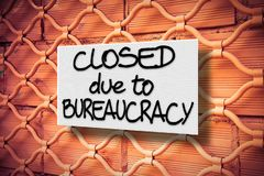 Closed due to bureaucracy - concept image with a warning sign against a closed metal shutter royalty free stock photo