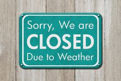 Closed due to weather sign. A teal sign with text Sorry we are closed due to weather on weathered wood stock photo