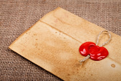 Closed envelope with sealing wax. Old styled closed envelope with red sealing wax stamp, burlap background Royalty Free Stock Image