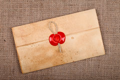 Closed envelope with sealing wax. Old styled closed envelope with red sealing wax stamp, burlap background Royalty Free Stock Photos