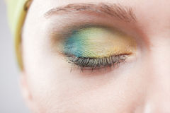 Closed eye with green-yellow makeup Stock Images