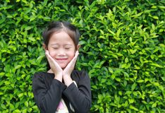 Free Closed Eyes Little Asian Girl Smiling And Holds Cheeks By Hand Against Leaves Wall Background In The Garden Royalty Free Stock Photography - 161343747