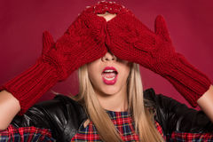 Closed eyes. Portrait of young beautiful woman in knitted hat and gloves closed her eyes eyes with her hands Royalty Free Stock Photo