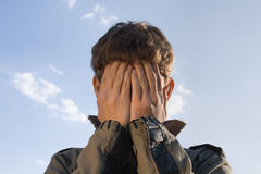 Closed face. Teenager has closed face. Blue sky background Royalty Free Stock Image