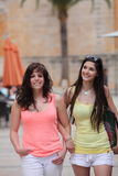 Closed Female Friends Strolling at the City Street Royalty Free Stock Image