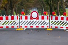 Closed Forbidden Road. Red and white colored street barrier on closed avenue road at countryside, grey asphalt copy space background royalty free stock photography