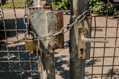 Closed gate with big steel chain and padlock.  Royalty Free Stock Photography