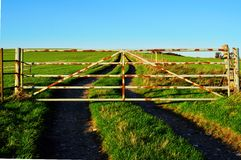 Closed Gate in Countryside. An old rusty metal gate across a track through a farmland field. This might suggest a concept of an obstructed path or lack of free Stock Image