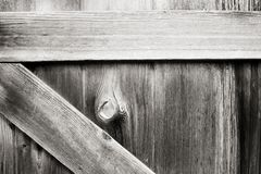 Closed gate with hole in knot of wood with grass visible on other side. Textured wooden gate with peephole and greener on the other side royalty free stock image