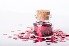 Closed glass jar filled with many red little hearts on white Royalty Free Stock Photos