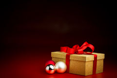 Closed Golden Box With Red Ribbon and Three Baubles Stock Photo
