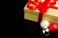 Closed Golden Box With Red Ribbon and Three Baubles Royalty Free Stock Photos