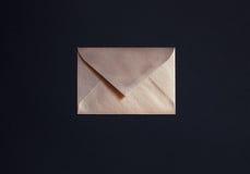 Closed golden envelope on black background Stock Images