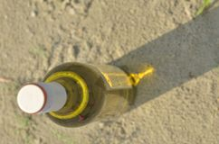 Wine bottle on sand, shadow Royalty Free Stock Images