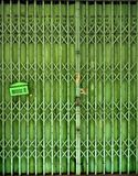 Closed retractable folding metallic gate. Closed green retractable folding metallic gate with mail box in front of traditional shop, vertical format Royalty Free Stock Photos
