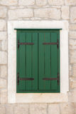 Closed green shuttered weathered wooden window Stock Images