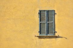 Closed green windows on yellow wall of old house in Florence cit. Y, Italy Stock Image