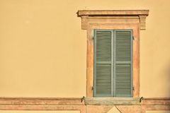 Closed green windows on yellow wall of old house in Florence cit. Y, Italy Stock Photo