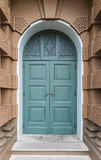 Closed green wooden door in European style with Brown building Royalty Free Stock Image