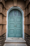 Closed green wooden door in European style with Brown Building Royalty Free Stock Images