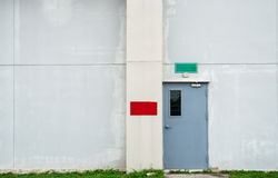 Closed grey door with green and red text box on white concrete wall. With copy space Stock Photo