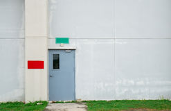 Closed grey door with green and red text box on white concrete wall. With copy space Royalty Free Stock Images