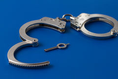 Closed handcuffs with key Stock Photography