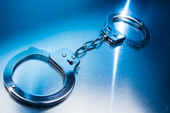 Closed handcuffs on a metallic background with dramatic lighting Royalty Free Stock Image